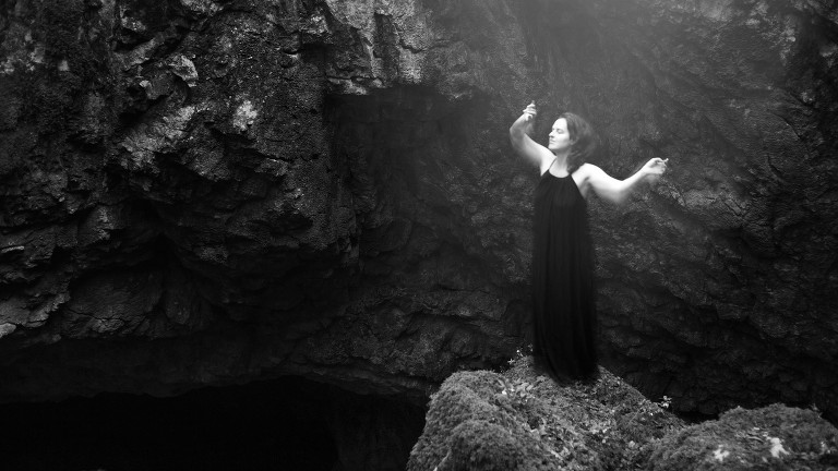 portrait of dancing woman in front of a cave
